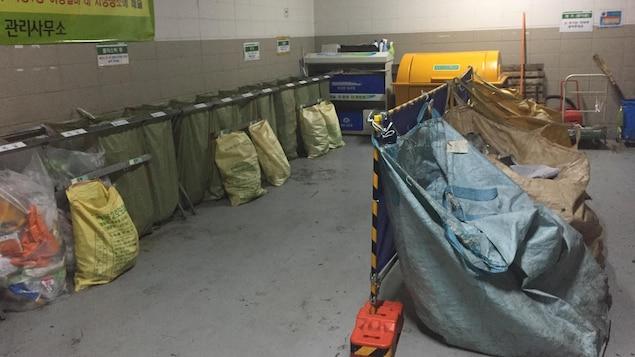 On voit de grandes poches dans une pièce bétonnée servant au tri des matières recyclables.