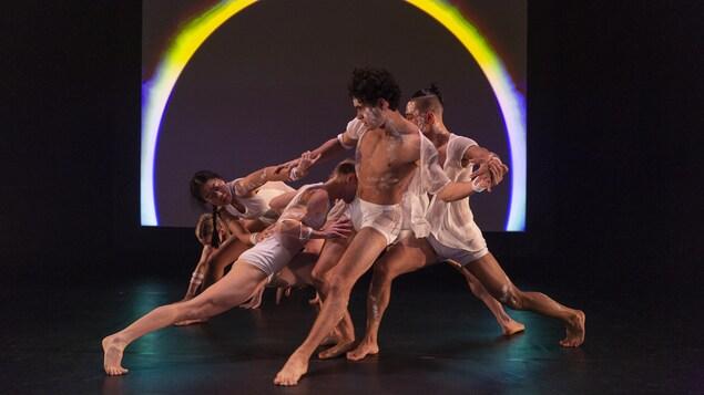 Des danseurs s'imbriquent devant un cercle lumineux.