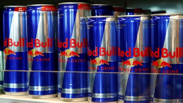 Des cannettes de Red Bull sont alignées sur une étagère commerciale.