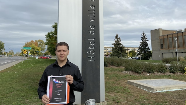 رجل يقف في الخارج بجانب عمود مكتوب عليه بالفرنسية مقرّ بلدية لافال وهو يحمل في يديه حزمة من الأوراق.