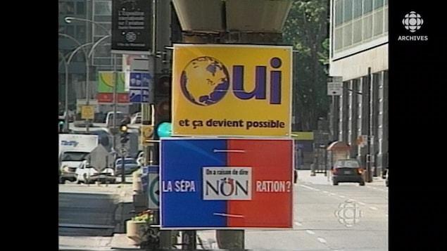 Une pancarte du camp du oui et du camp du non sur un poteau sur un boulevard au centre-ville de Montréal.