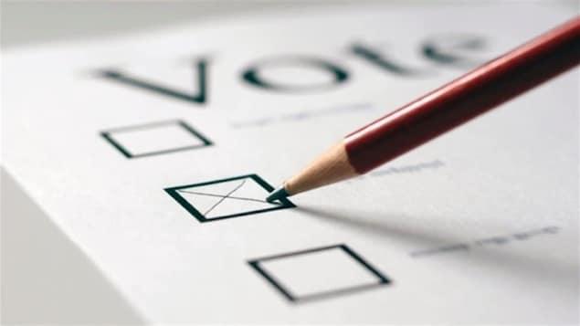 Plan serré d'un crayon de plomb qui trace une croix sur un bulletin de vote.