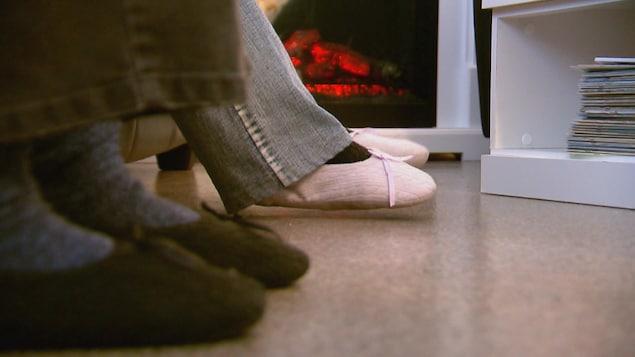 Deux paires de pieds avec des pantoufles, un foyer en arrière-plan.