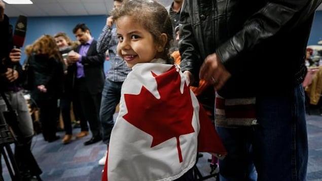 Une petite fille souriante est enveloppée dans un drapeau canadien lors d'un point de presse.