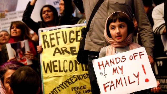 Une petite fille tient une affiche sur laquelle est écrit : «Ne touchez pas à ma famille!»