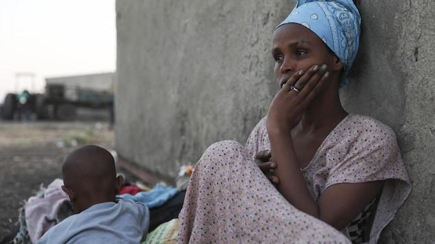 Une femme est assise par terre, adossée à un mur, près de son garçon.