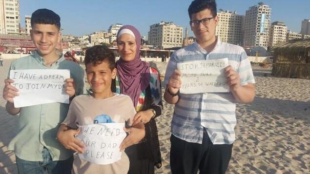 L'épouse et les trois fils d'Abdallah Alhamadni sur la plage tenant des affiches qui demandent de pouvoir venir au Canada.