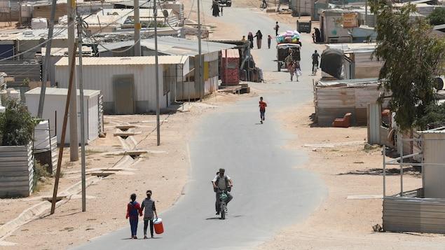 Des réfugiés syriens sur une route poussiéreuse.