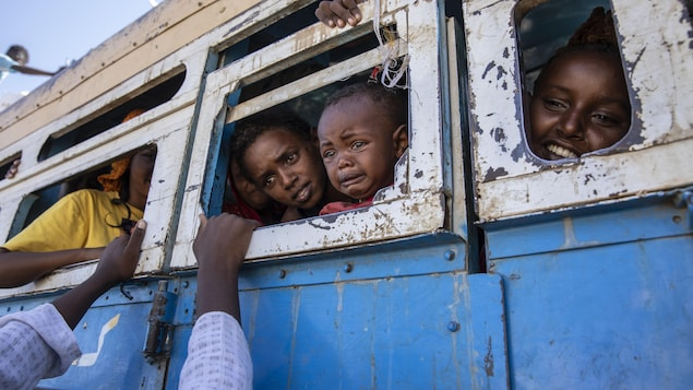 Plusieurs enfants regardent par les fenêtres sans vitre d'un autobus vétuste. Le plus jeune est en pleurs.