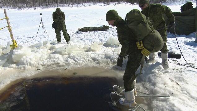 Un militaire se jette à l'eau avec des raquettes aux pieds et un sac sur son dos.
