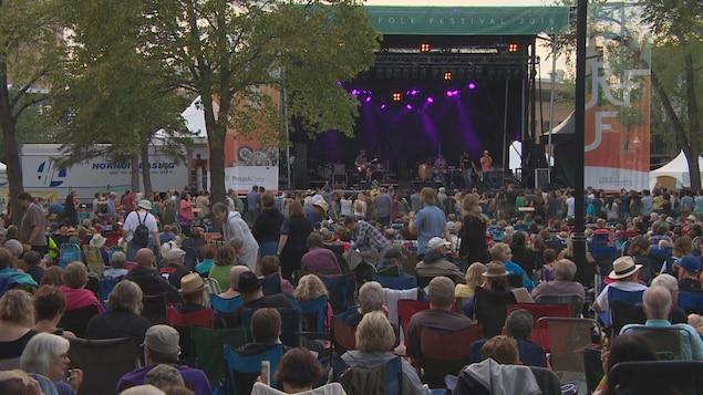 Des amateurs de musique sont assis devant une scène dans un parc.