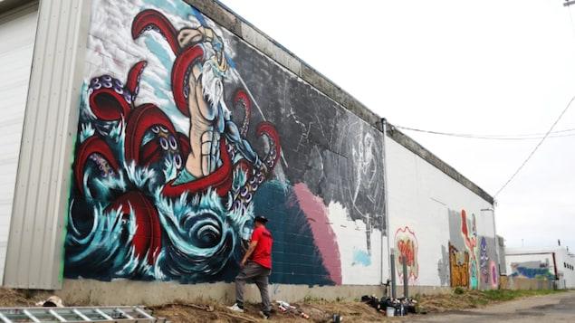 Un artiste peint un graffiti sur un mur à Regina.