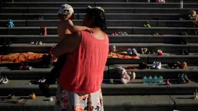 Une femme avec son petit-fils dans les bras est photographiée le dos tourné devant l'assemblée législative de Victoria.