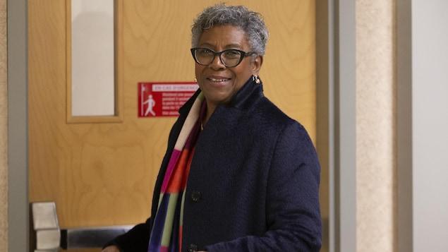 Une femme souriante photographiée en gros plan devant une porte.