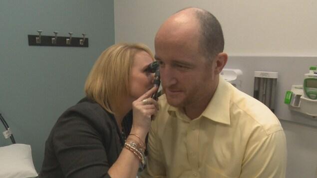 Un patient se fait ausculter par un médecin.