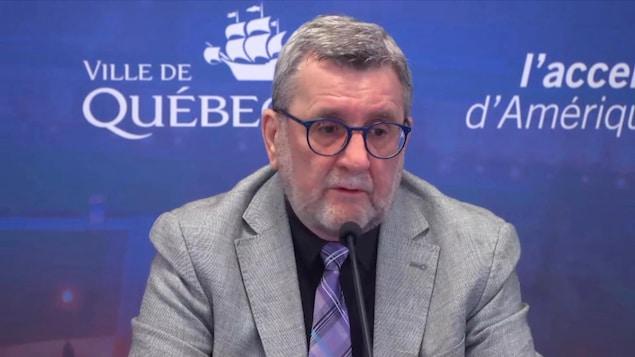 Régis Labeaume devant le logo de la ville de Québec en conférence de presse.