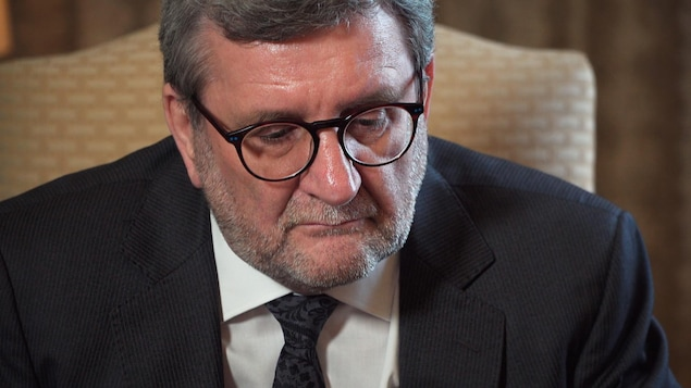 Régis Labeaume avec des lunettes, un veston et une cravate, le regard sérieux, regarde vers le bas