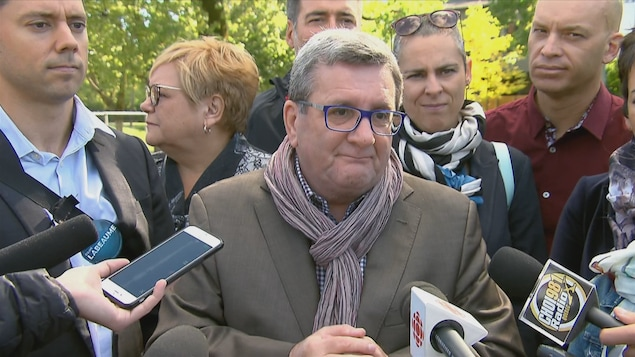 Régis Labeaume répond aux questions des journalistes entourés des candidats de son équipe.