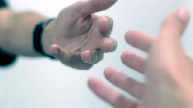 Une main tendue, une autre va pour l'attraper.