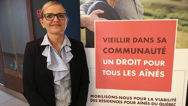 Une femme pose à côté d'une affiche montrant le slogal «Vieillir dans sa communauté, un droit pour tous les aînés».