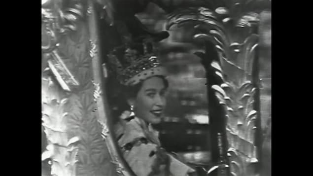 La reine Elisabeth II, souriante, assise dans le carrosse royal avec sa grosse couronne sur la tête.