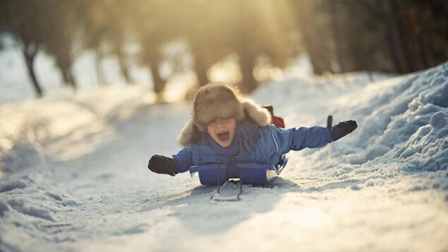 Un garçon dévale une pente assis sur son traîneau à neige.