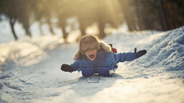 Un garçon dévale une pente couché sur son traîneau à neige en riant.