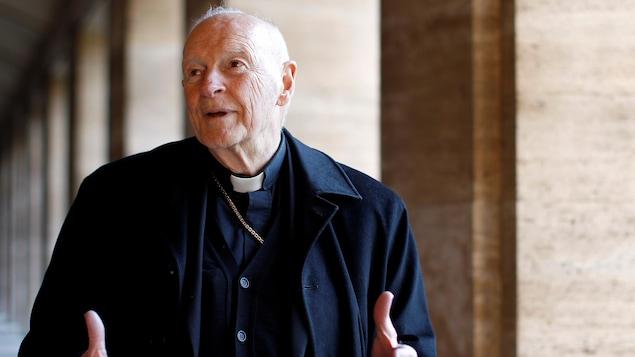 Un vieil homme portant l'habit d'un cardinal dans un corridor.