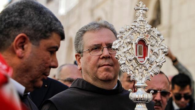 Un religieux au début d'une procession tient la relique devant lui.