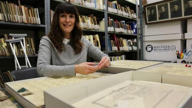 Une femme sourit à la caméra avec des archives derrière elle. Elle tient dans ses mains une petite relique.