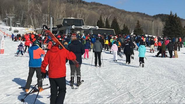 Des skieurs et des planchistes font la file pour utiliser la remontée mécanique du Mont Sainte-Anne.