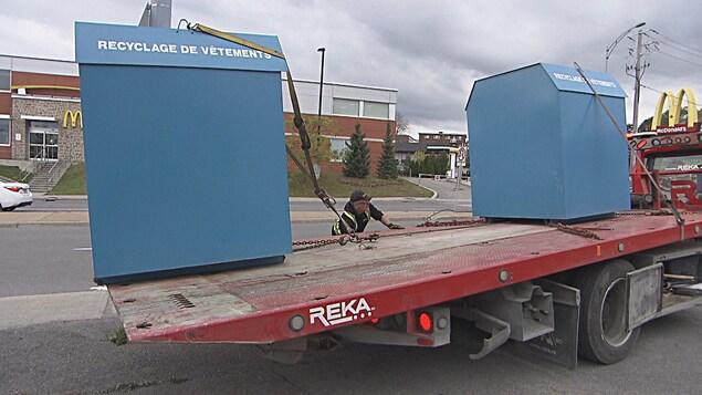 Deux boîtes de dons bleues en train d'être chargées sur un véhicule de remorquage