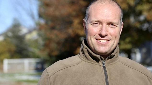Un homme souriant devant un arbre jauni par l'automne