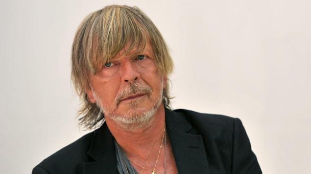 Le chanteur français Renaud porte un veston noir et plusieurs chaînes en or au cou.