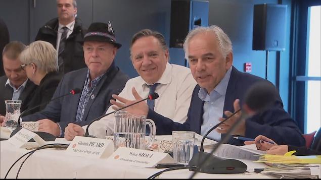 François Legault est souriant pendant qu'il écoute Ghislain Picard prendre la parole.