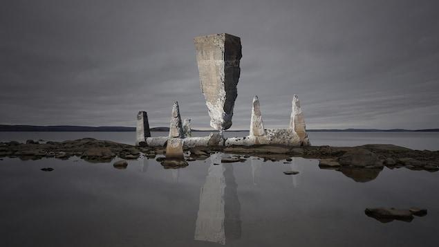 Photo d'une structure géante en roches sur une étendue d'eau.