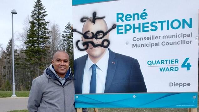 Le candidat René Ephestion à côté d'une affiche életorale.