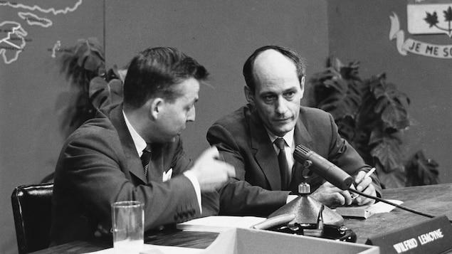 Dans un studio de télévision, assis à une table surmontée d'un micro de table, l'animateur Wilfrid Lemoine discute avec René Lévesque, nouveau député du Parti libéral du Québec, dans la circonscription de Montréal-Laurier.