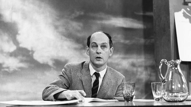 Dans un studio de télévision, assis à une table où reposent une carafe et deux verres, l'animateur René Lévesque s'apprête à tourner avec son index la feuille devant lui.