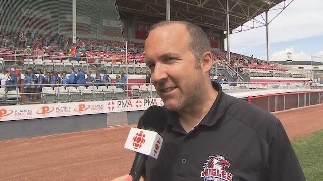Sur le terrain de baseball, il répond aux questions de la journaliste.