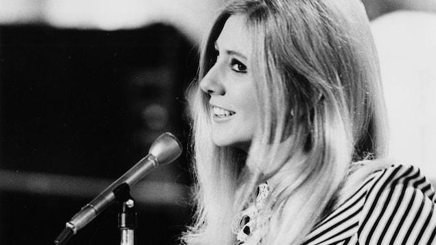 Renée Martel qui chante derrière un micro.
