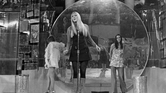 Renée Martel debout derrière le micro avec deux danseuses derrière elle.