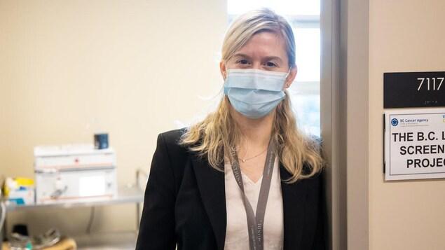 Une femme qui porte un masque médicale est appuyée dans le cadre d'une porte.
