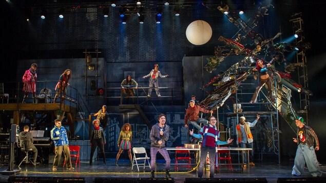 Tous les comédiens de la pièce Rent sont sur la scène et l'acteur principal au centre chante.