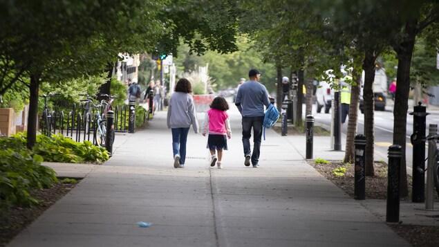 Des parents avec leur fille sur le trottoir couvert d'arbres feuillus.