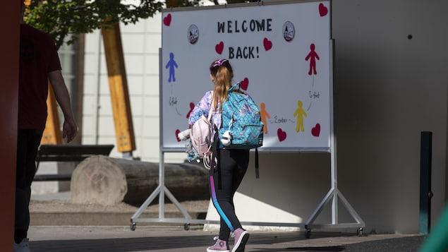 Jeune fille avec un sac sur le dos devant une affiche souhaitant un bon retour à l'école.