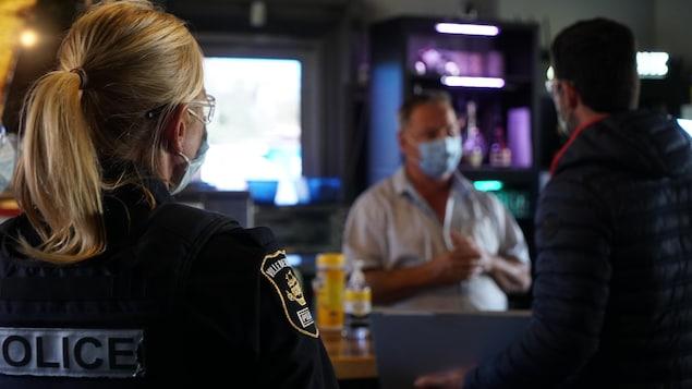 Une policière regarde un employé discuter avec un client dans un bar.