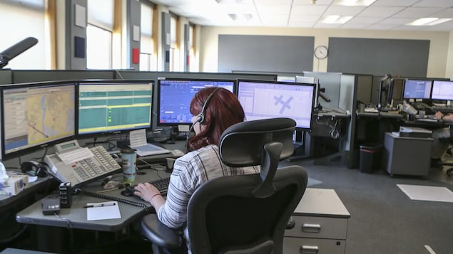 Une répartitrice médicale d'urgence est en train de travailler. Elle fait face à quatre écrans.