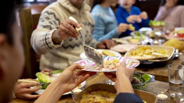 Un homme sert un invité lors d'un souper.