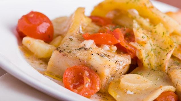On voit un repas de poisson, de tomates et de pommes de terre, servi dans une assiette.
